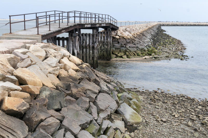 Bridge over shallow waters. Gap in the breakwater at Plymouth, Massachusetts enables small boats to take a shortcut to leave the harbor when tides are higher stock image
