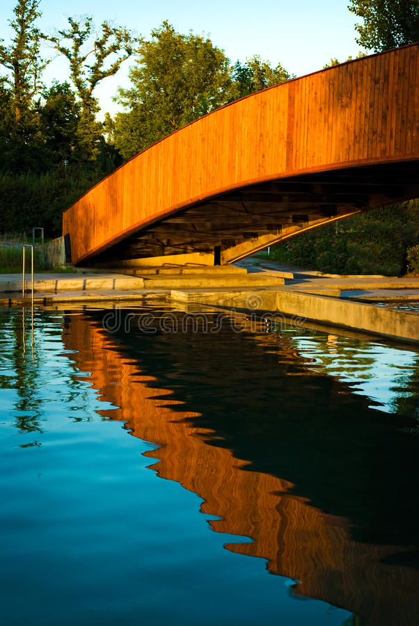 Bridge over swimming pool. Wooden bridge over swimming pool enlighten by setting sun on a calm summer twilight reflecting in water stock images