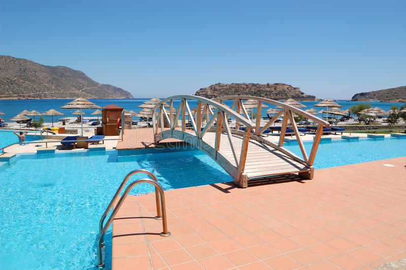 Bridge over swimming pool to the beach. At luxury hotel, Crete, Greece stock photography