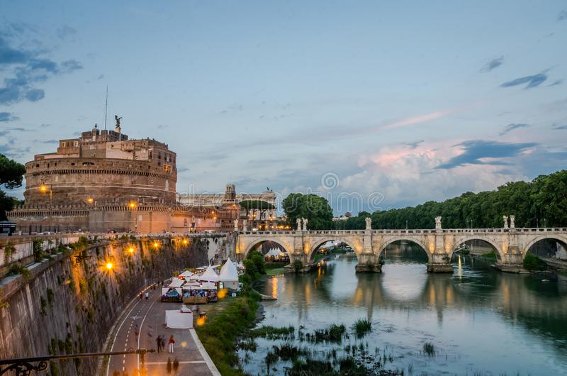 Bridge over the Tiber River near the Castle of Angel - Vatican prison at sunset on an evening summer day in Rome, Italy. Bridge over the Tiber River at sunset on royalty free stock images