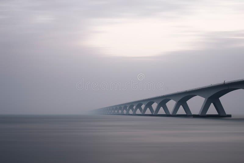 Bridge over water in fog royalty free stock image