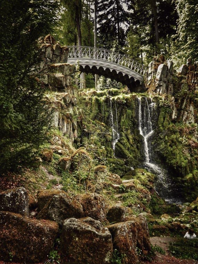 Bridge over a waterfall at Bergpark Wilhelmshöhe in Kassel, Hesse, Germany (UNESCO world heritage site) royalty free stock photo