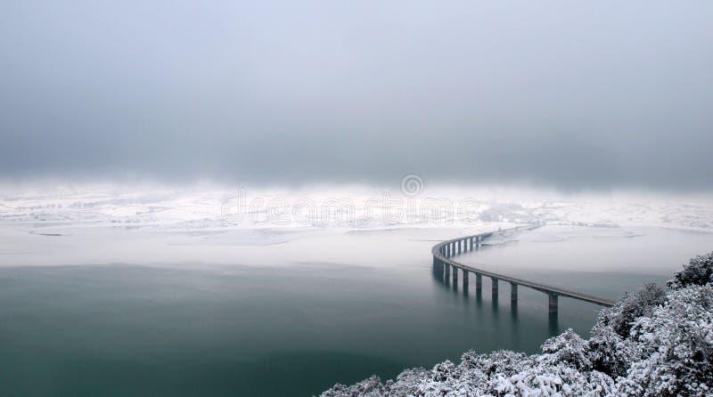 Bridge over wintry lake royalty free stock image