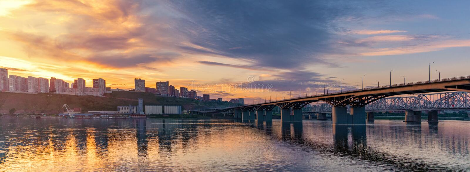 Bridge over the Yenisei river, evening sunset. Krasnoyarsk, Russia. panorama of the evening city stock image