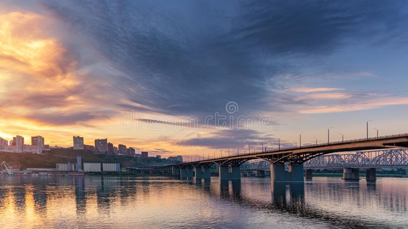Bridge over the Yenisei river, evening sunset. Krasnoyarsk, Russia. panorama of the evening city stock images