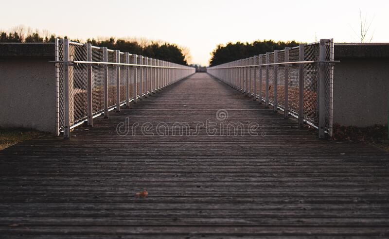 Bridge in a park when sun sets royalty free stock photo