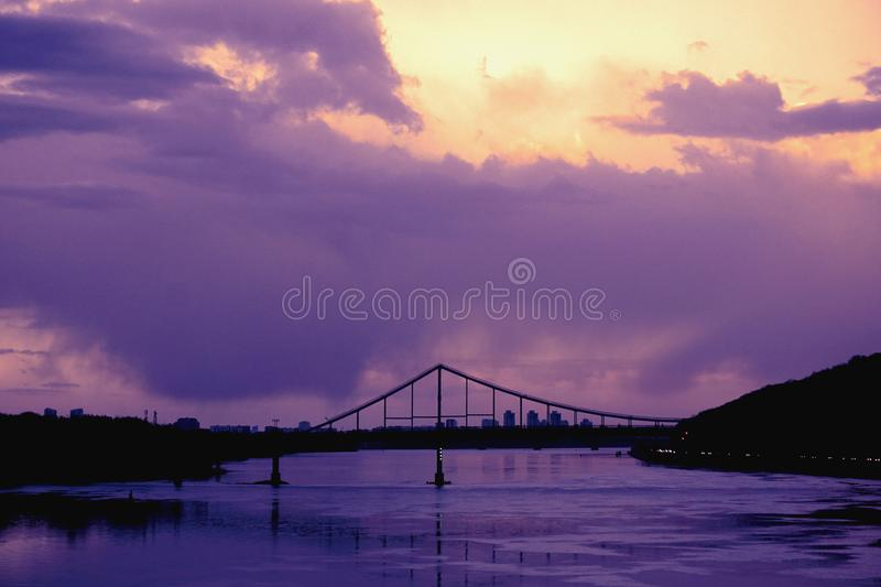 Bridge reflection in water surface of river Dnieper duaring sunset time. Toned image: purple, violet, yellow, orange colors stock images