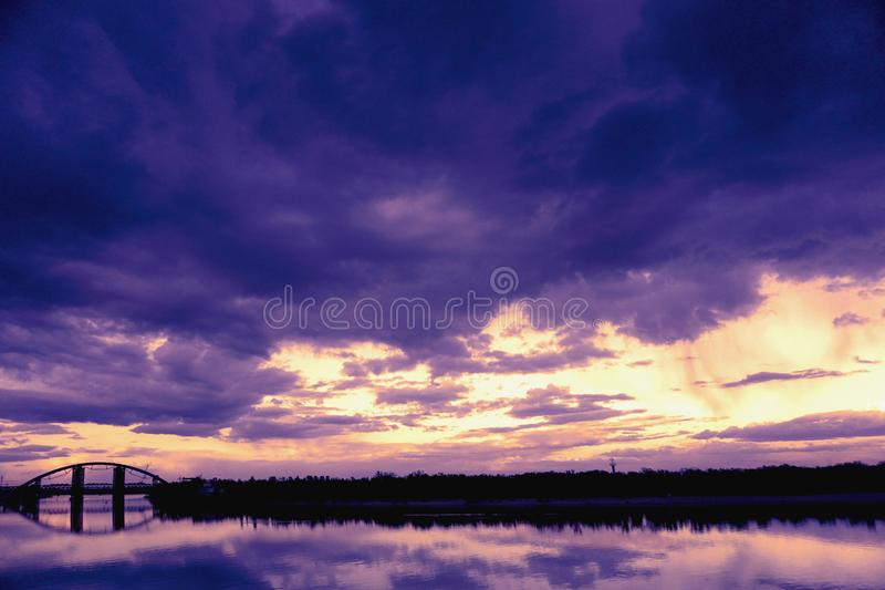 Bridge reflection in water surface of river Dnieper duaring sunset time. Toned image: purple, violet, yellow, orange colors stock photography
