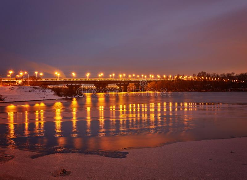 Bridge on the River Dnieper in the evening. Lantern light is ref. Lected in the frozen ice, city, Ukraine stock photography