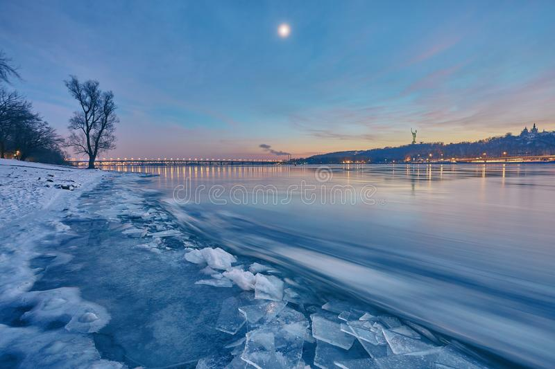 Bridge on the River Dnieper in the evening. Lantern light is ref. Lected in the frozen ice, city, Ukraine stock photos