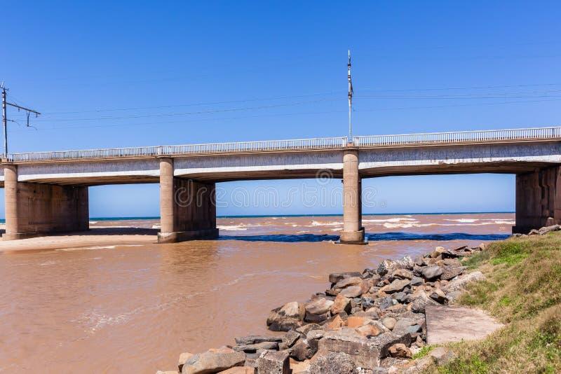 Bridge River Ocean. Bridge along beach coastline with river flooding brown water into ocean stock images