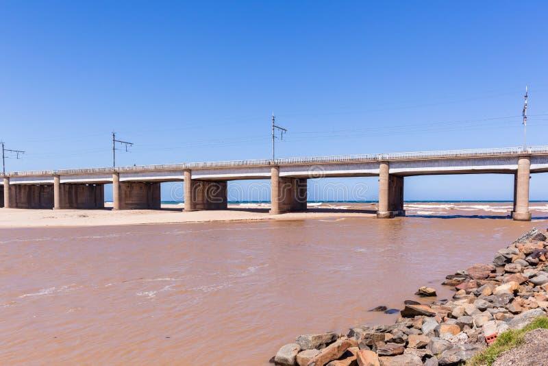 Bridge River Ocean. Bridge along beach coastline with river flooding brown water into ocean stock photography