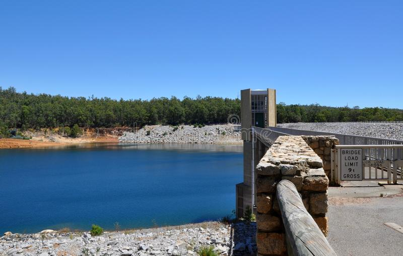 Bridge at Serpentine Dam. Elevated bridge at the Serpentine Dam with the Serpentine River surrounded by lush greenery under a blue sky in Serpentine, Western royalty free stock image