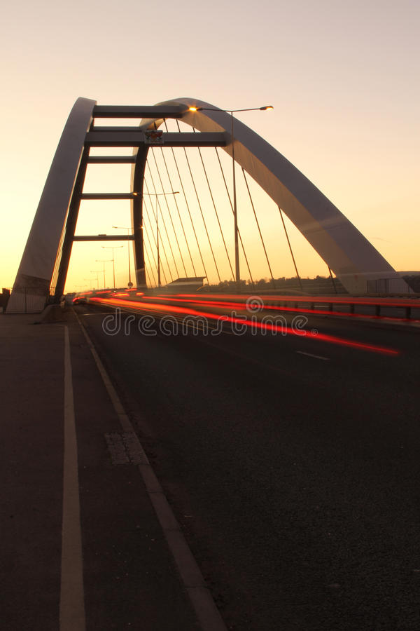 Bridge silhouette with colored sky. Silhouette of tall bridge with bright colored sky and light trails from traffic. Background, concept of travel, exploration stock photos