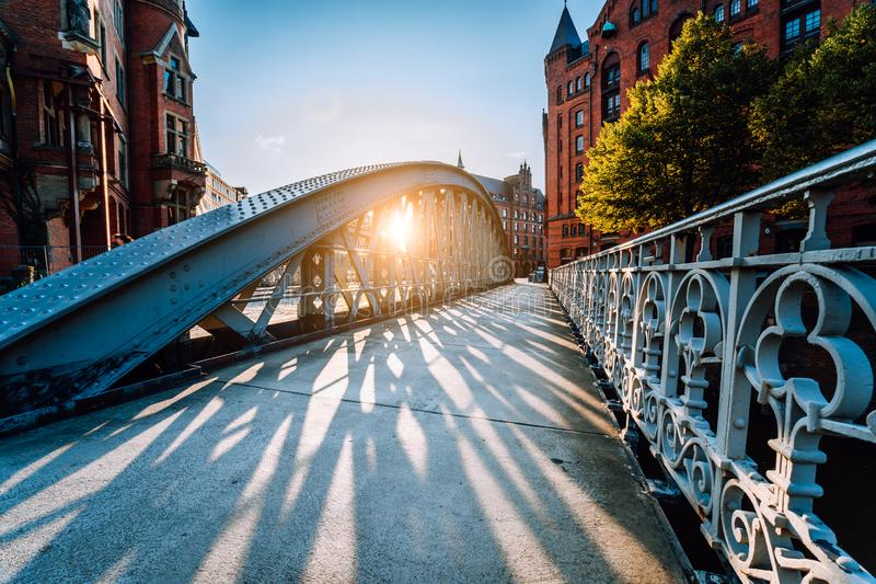 Bridge in the Speicherstadt old warehouse district of Hamburg with sunset evening light. Long shadows in golden hour stock images