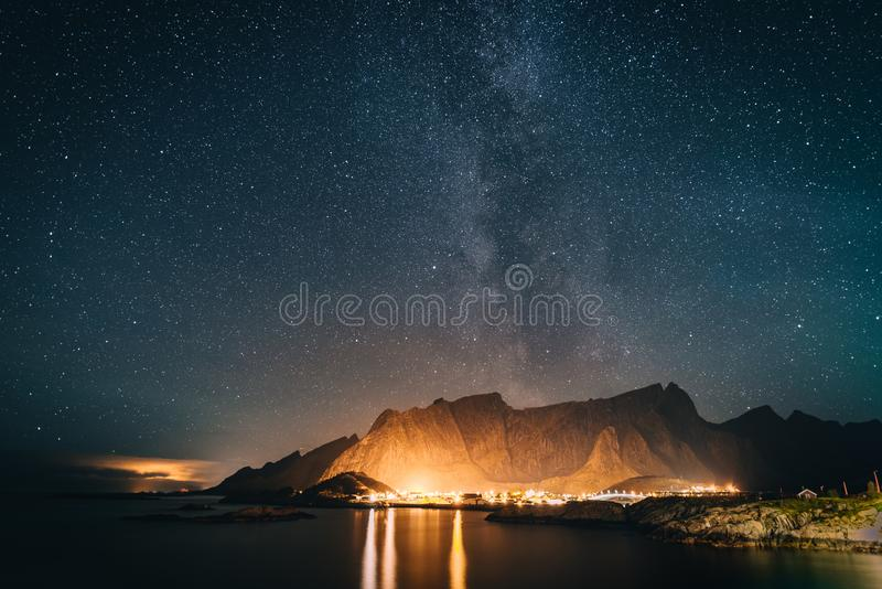 Bridge and starry sky with Milky Way over mountains reflected in water. Village of Reine Hamnoy Sakrisoy Lofoten islands stock image