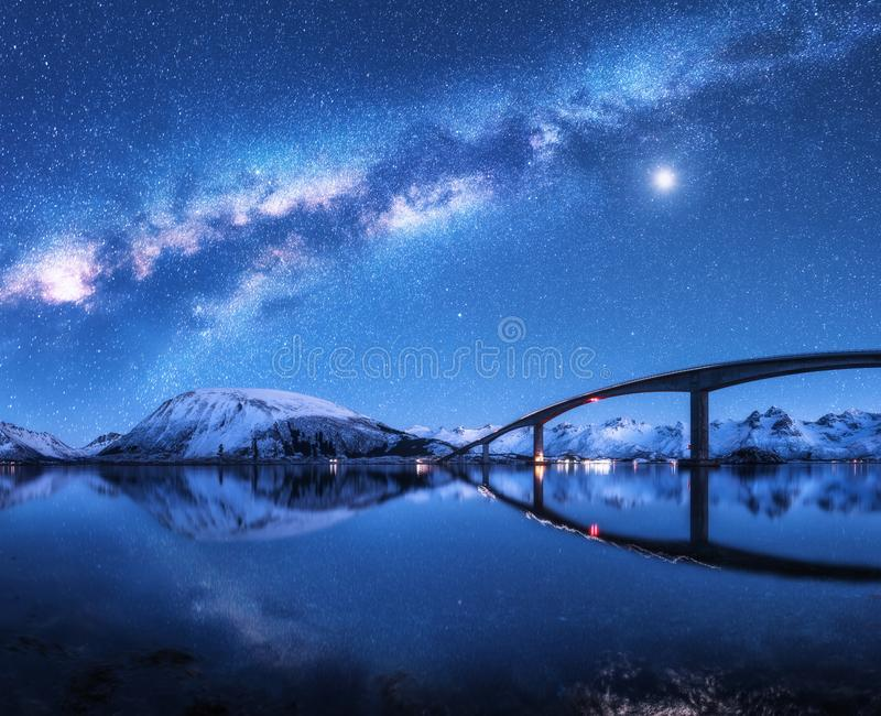 Bridge and starry sky with Milky Way over snow covered mountains royalty free stock image