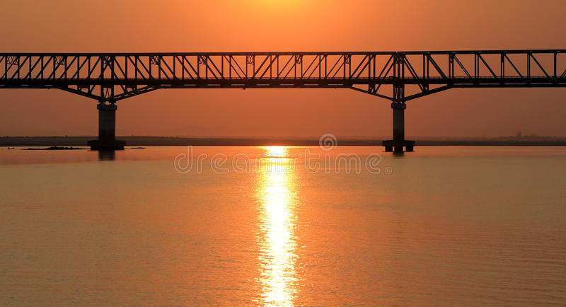 The bridge at sunset on the Irrawaddy River. The golden sun, rippling on the water which has turned red during the sunset on the Irrawaddy River, the railway royalty free stock photos