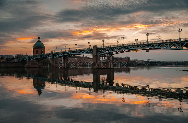 Bridge and sunset. The sunset is reflected in the calm waters of the river royalty free stock photography