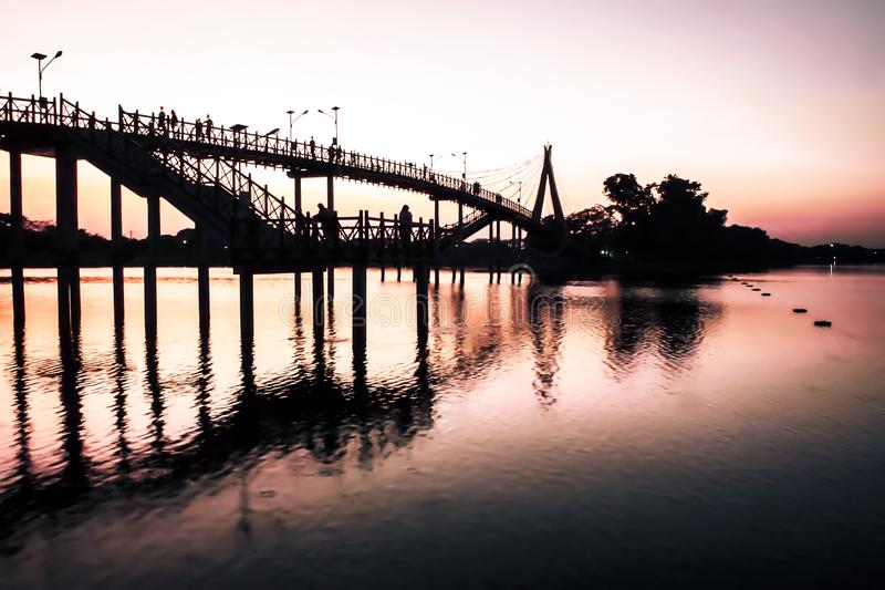 Bridge at sunset .Vanilla sky in blur and pink shade with crowd on the bridge . silhouette photography.  royalty free stock image