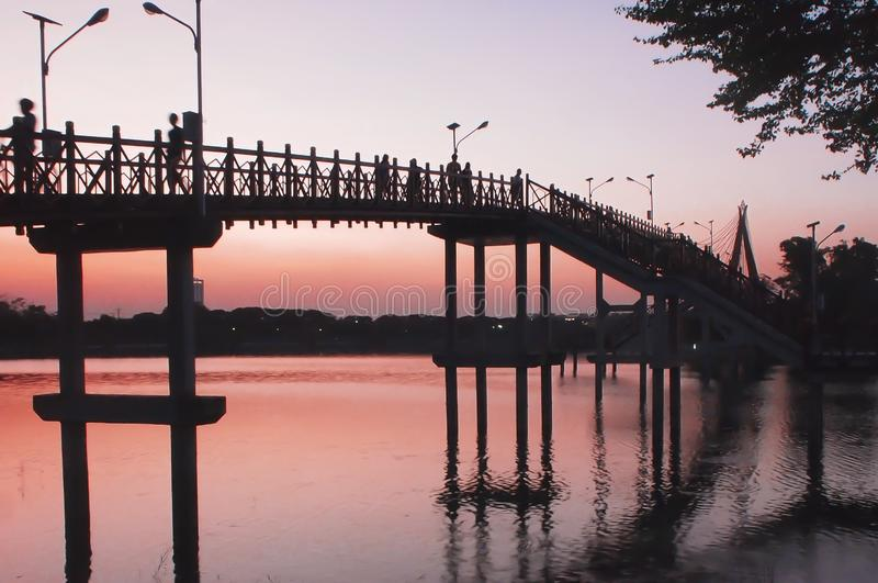 Bridge at sunset .Vanilla sky in blur and pink shade with crowd on the bridge . silhouette photography.  stock photo