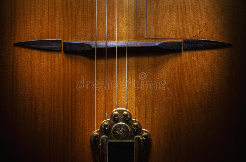 Bridge And Tailpiece. Bridge known as mustache and golden tailpiece, parts of an old acoustic gypsy guitar royalty free stock images