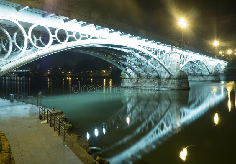 Bridge of Triana and Isabel II of Seville - Puente de Triana e Isabel II de Sevilla. Side view of the Triana bridge illuminated in Seville also called Isabel II royalty free stock images