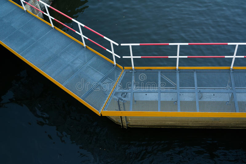 Bridge and walkway with metal bar grating and handrail. Dark water under platform. Detail of industrial complex underexposure stock photography