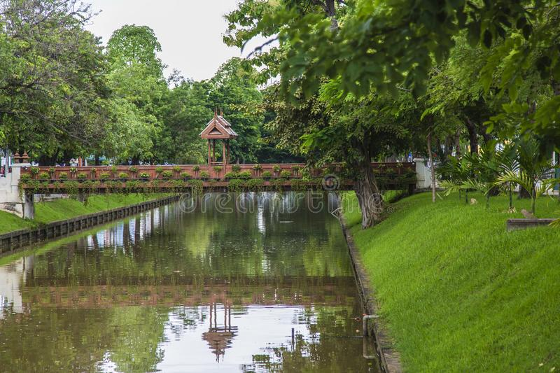 Bridge Over Mote in Chaing Mai. Bridge walkway  mote in chaing mai thailand. surrounded by lush greenery. canal old city trees water foot footbridge royalty free stock photo