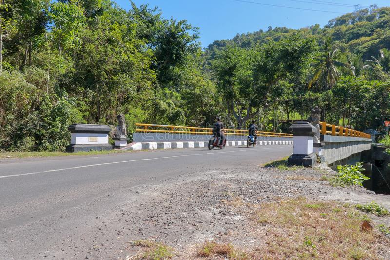 Bridge with yellow metal railing over river in mountains on Bali island. Decorative stone statues. People ride motorbikes. royalty free stock images