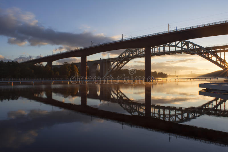 Bridges reflected in water at beautiful, early dawn. Bridges reflected in calm water at beautiful, early autumn dawn. Golden rays and misty sea stock image