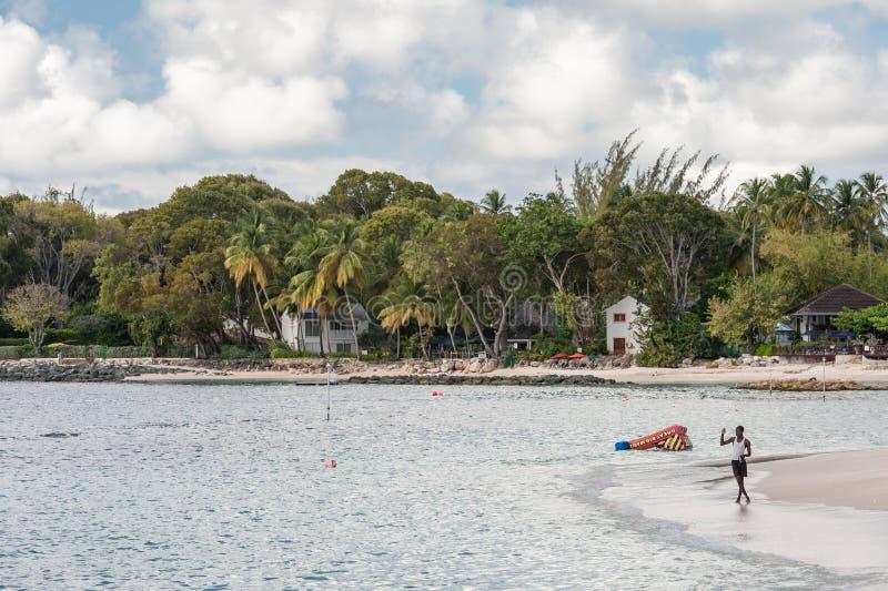 BRIDGETOWN, BARBADOS - 11 DE MARZO DE 2014: Mar del Caribe y playa con el pescador local en Barbados Isla del mar del Caribe imágenes de archivo libres de regalías