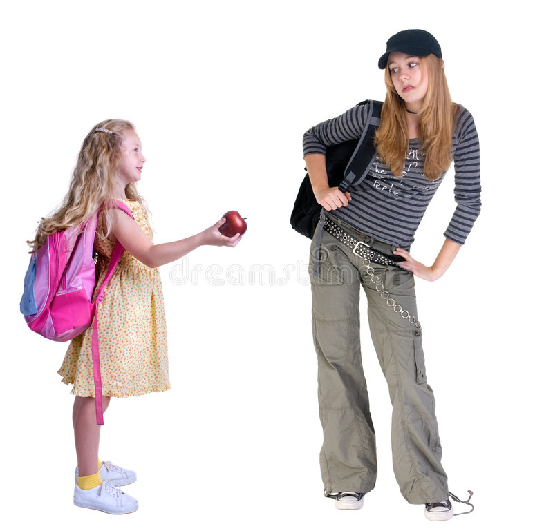 Bridging the Gap. A young girl offers an apple to older grunge looking high school student. Young kids are not so quick to judge by looks alone