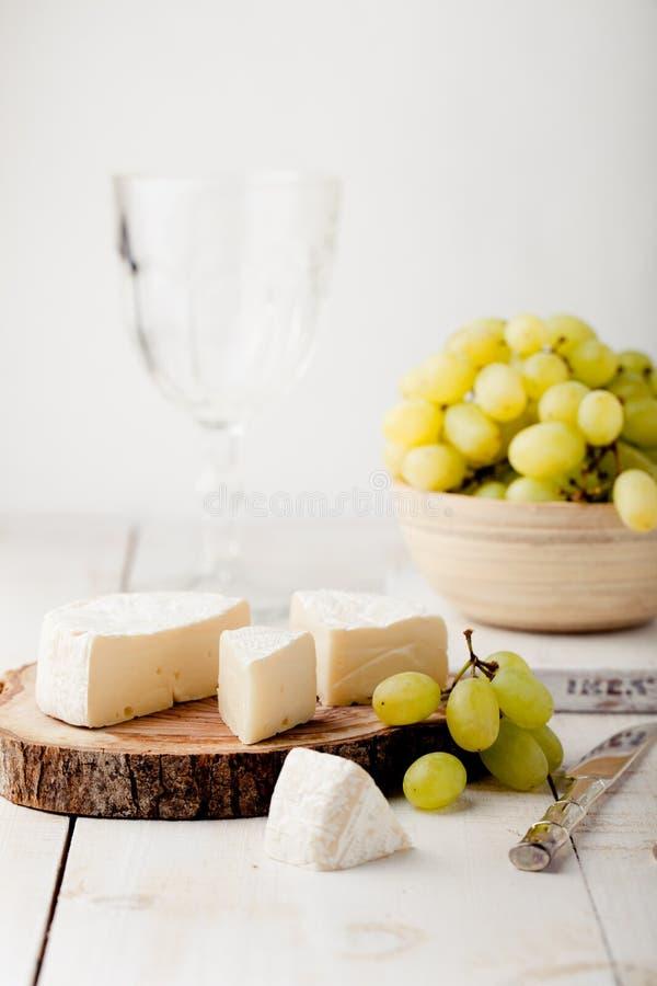 Brie camembertost med den nya druvan, vinexponeringsglas royaltyfri bild