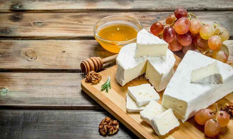 Brie cheese with grapes, nuts and honey on the Board. On a wooden background stock photography