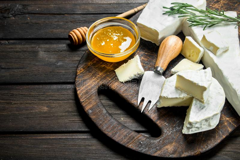 Brie cheese with honey and rosemary. On a wooden background royalty free stock image