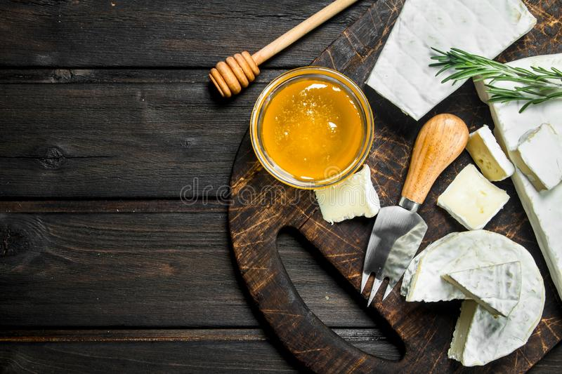 Brie cheese with honey and rosemary. On a wooden background stock images