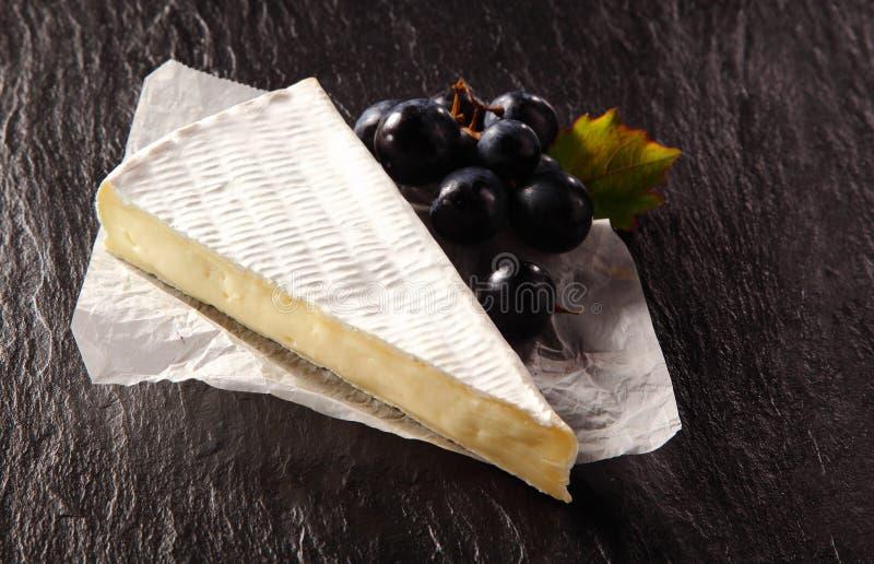Brie Cheese Wedge och svarta druvor på tabellen fotografering för bildbyråer