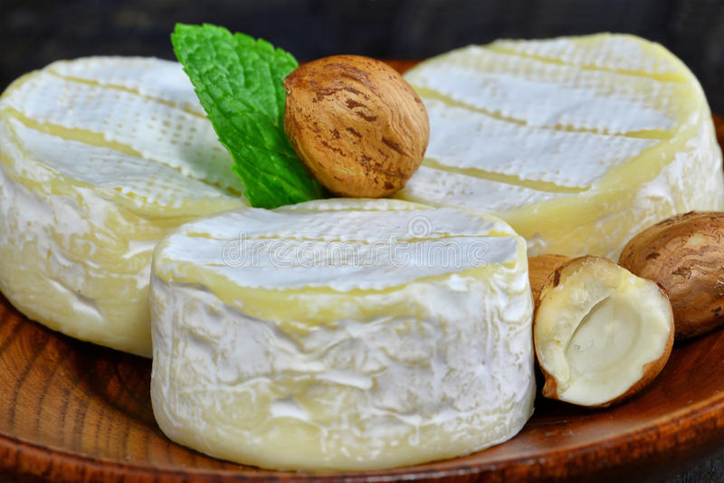 Brie cheese wheels with white mold. On wooden plate stock photos