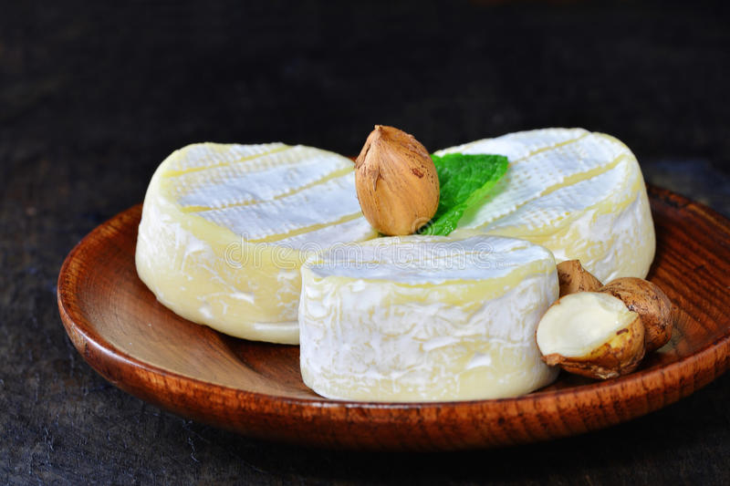 Brie cheese wheels with white mold. On wooden plate royalty free stock images