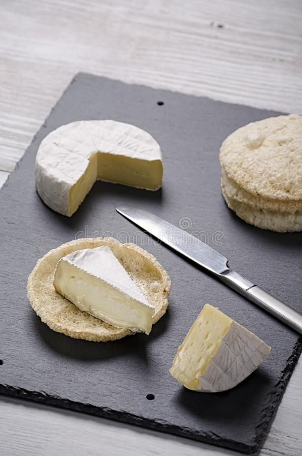 Brie de famille cheese and small round loaves lie on a slate Board on a white wooden background, round cheese, sliced cheese on stock photos