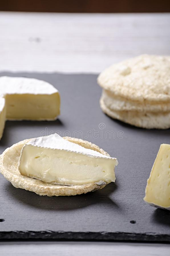 Brie de famille cheese and small round loaves lie on a slate Board on a white wooden background, round cheese, sliced cheese on royalty free stock images