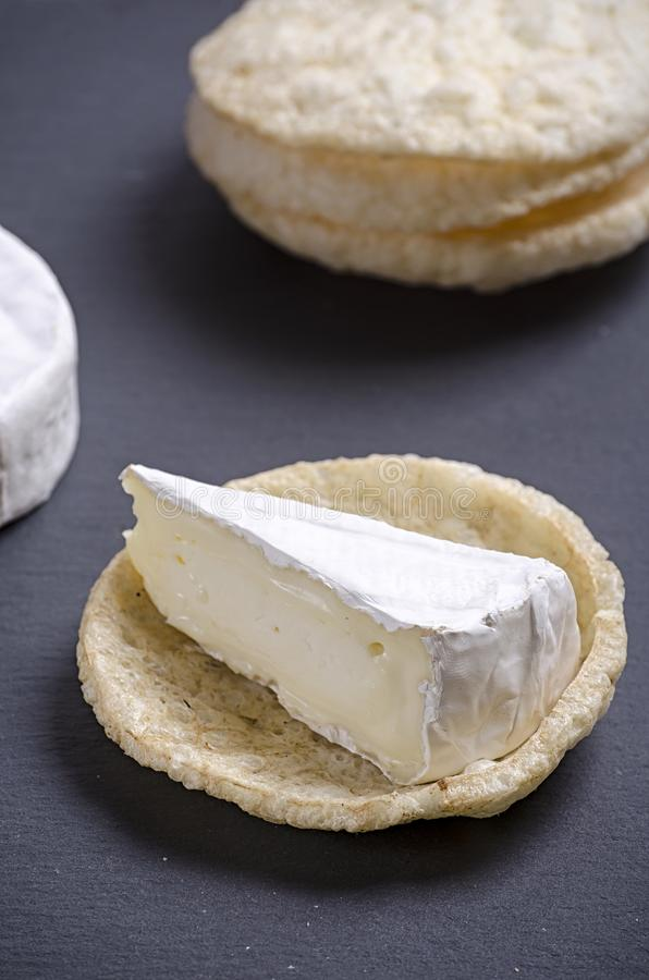 Brie de famille cheese and small round loaves lie on a slate Board on a white wooden background, round cheese, sliced cheese on stock image