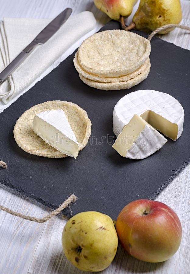 Brie de famille cheese and small round loaves lie on a slate Board on a white wooden background, round cheese, sliced cheese on royalty free stock photos