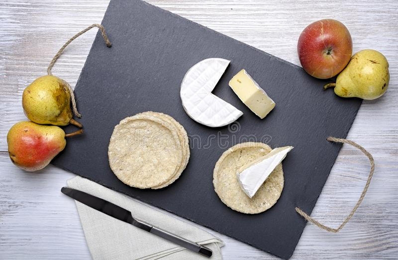 Brie de famille cheese and small round loaves lie on a slate Board on a white wooden background, round cheese, sliced cheese on stock images