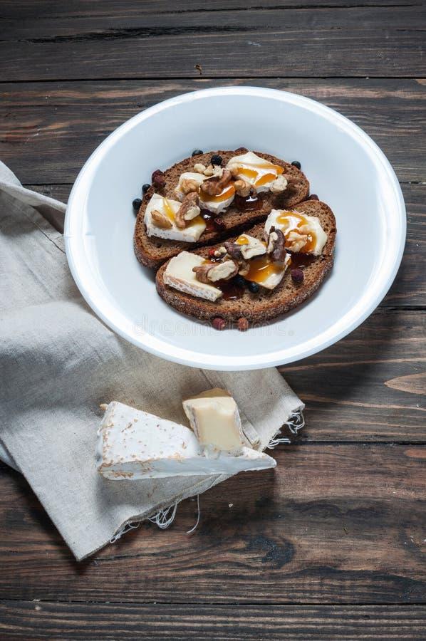 Brie derretido com mel, pinhões e nozes no pão escuro fotos de stock royalty free