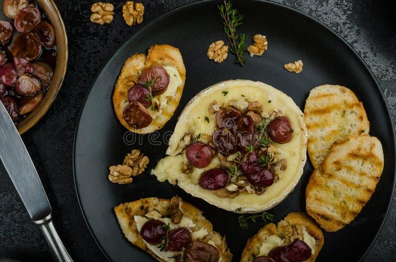 Brie gebacken mit Nüssen und Trauben stockfotos