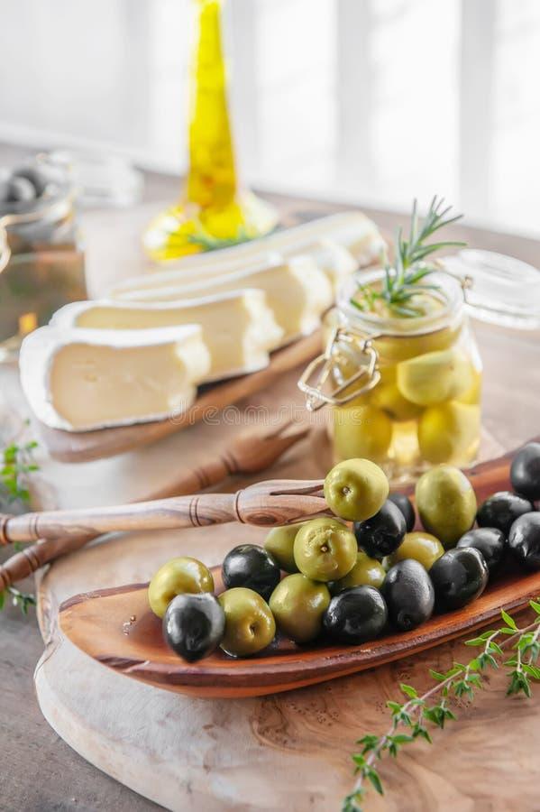 Brie invecchiato su un piatto bianco con la tavola di legno delle erbe della Provenza e delle olive immagine stock