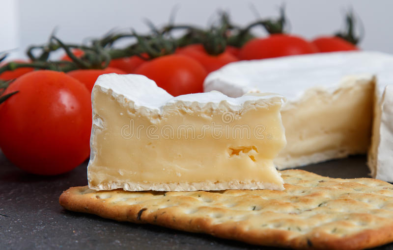 Brie soft cheese with crackers and tomato on a grey slate boar stock images