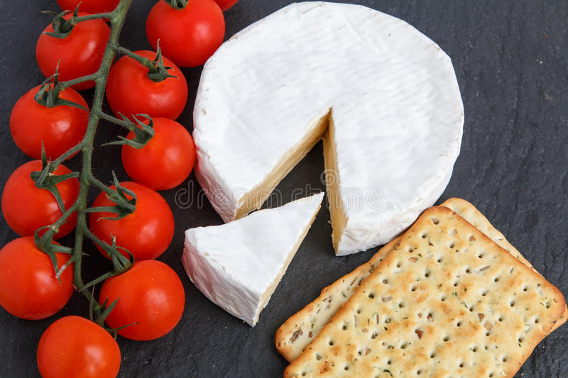 Brie soft cheese with crackers and tomato on a grey slate boar royalty free stock images